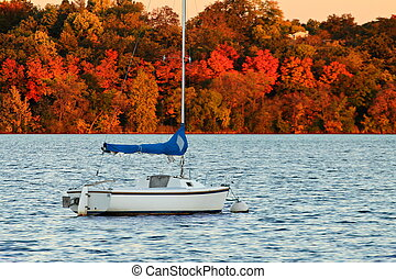 Lake Harriet Sail Boat in Autumn - A sail boat is moored at...