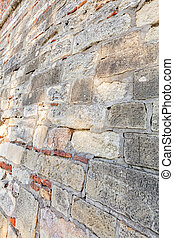 old stone wall - old wall made of stone and bricks, note...