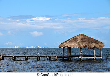 Thatched Cabana with Cancun on the Horizon - A lone thatched...