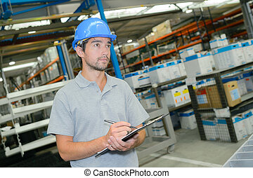 Man in warehouse writing on clipboard