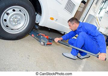 Mechanic pushing jack under vehicle