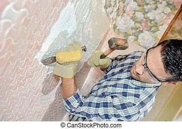 Mason chiping away at surface of a wall