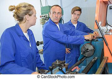 mujer, hombres, dos, Mirar, maquinaria, Utilizar