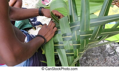 African builds basket from palm leaves at the beach
