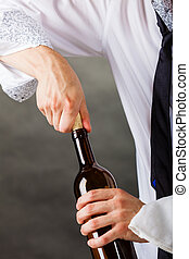 Waiter opens wine bottle. - Winery serving tasting alcohol...