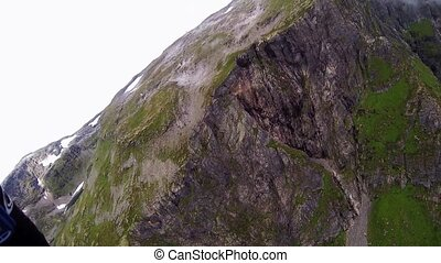 Skydiver parachuting above mountains covered by greenery and...