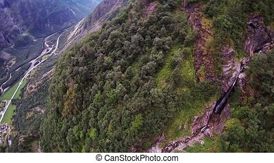 Skydiver parachuting above mountains covered by green trees. Extreme. Landscape