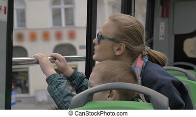 Mother and son looking at city from double-decker bus -...