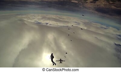 Skydivers jump from airplane above arizona. Grey sky. Making...