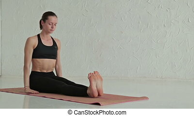 Young sporty woman practicing yoga - sage marici twisting...
