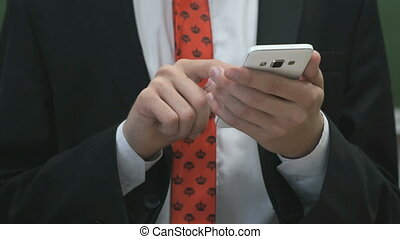Businessman writing the text using a smartphone -...