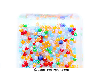 Colorful beads in box on white background