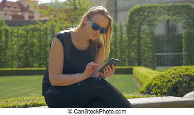 Woman spending leisure time with cell in green park - Young...