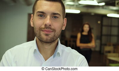 Portrait of handsome confident young businessman standing...