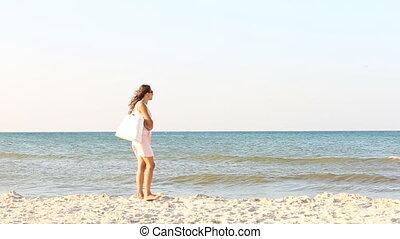 girl with a bag on the beach