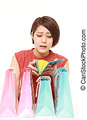 wasteful Japanese woman with shopping bags looking her empty wallet