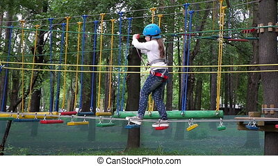 girl passes a rope obstacle course in park