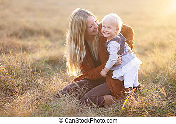 Happy Mother and Laughing Baby Girl Playing outside in Autumn