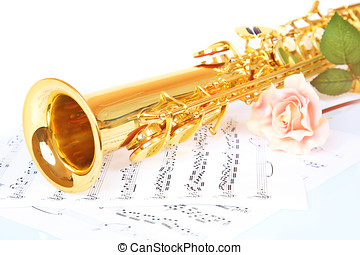 Pink rose, saxophone and music sheet on a white background