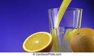 Orange juice pouring in glass on color background