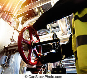 factory worker turning valve