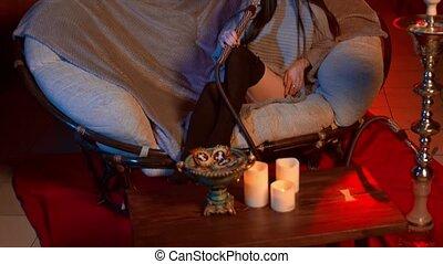 Beautiful brunette smokes a hookah in the loft room -...