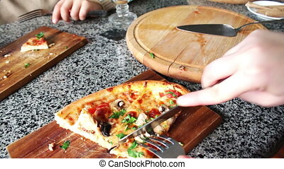 People eat large pieces of hot pizza - Mother with child...