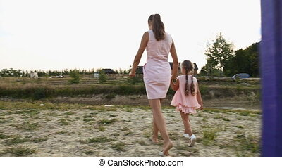 Mom with daughter walking near the pond