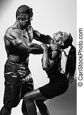 Muscular man strangling a beautiful woman. A man in conflict...
