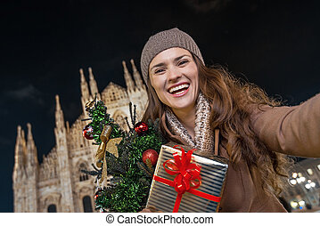woman with Christmas tree near Cathedral in Milan taking...
