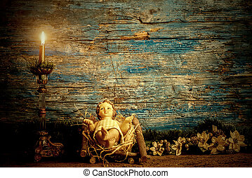 Christmas card, baby Jesus in his crib and vintage candle in...