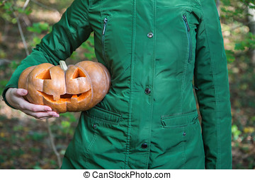 Woman holding Halloween pumpkin carved with an angry face and smile
