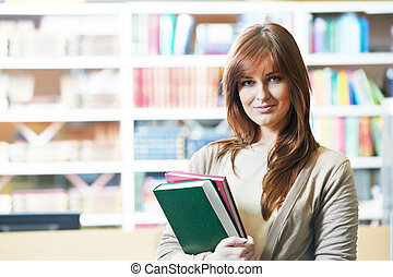 young female adult student with book in library - young...