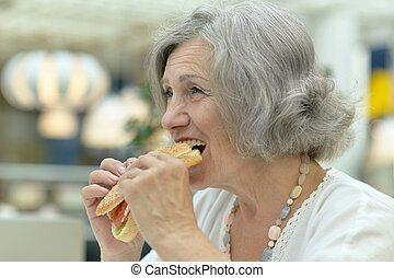 Happy elderly woman eating fast food