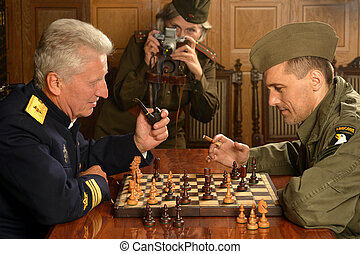 Military mature general on the table with soldiers playing...