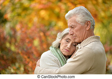 Sad elderly couple standing embracing outdoors - Portrait of...