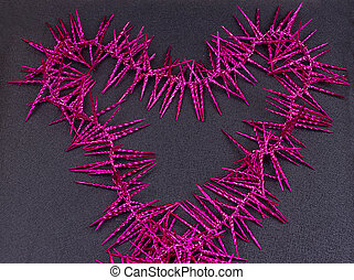garland of purple christmas beads forming a heart shape on...