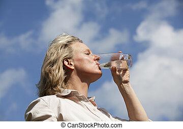 woman drinking water - A beautiful mature blond woman...