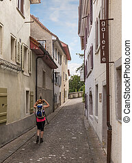 Traveler walking down narrow street between apartments in...