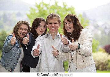 smiling teenagers posing thumbs up - Four happy smiling and...