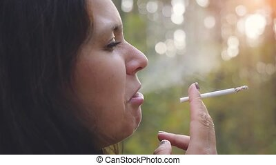 Close up of Young woman smoking a cigarette outdoor in slow...