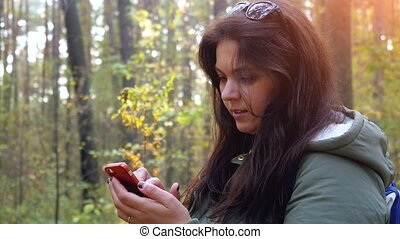 Young beautiful woman uses the phone in the autumn forest....