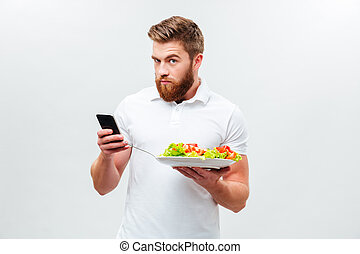 Young man holding plate with vegetable and using mobile...