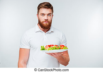 Portrait of a bearded man holing plate with fresh salad and...