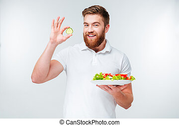 Smiling young bearded man holding plate with salad and...