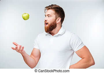 Happy casual young man throwing up an apple - Happy casual...