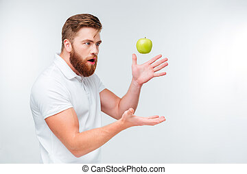 Funny bearded man throwing up a green apple isolated on...