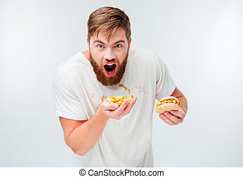 Hungry bearded man in filthy shirt eating hamburgers...