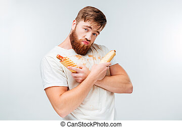Young bearded man in filthy shirt holding two hotdogs...