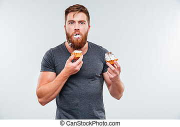 Filthy bearded young man eating cream cakes isolated on...